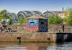 Mit Grafitti bunt besprühter Bunker am Billehafen / Oberhafenkanal - im Hintergrund die Freihafenelbbrücken.