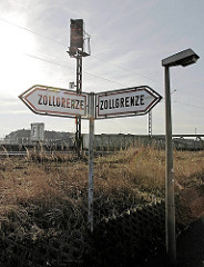 Schilder Zollgrenze - im Hintergrund Wohngebäude Hamburg Veddel.