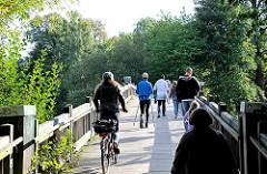 Holzbrücke am Ufer der Alster in Hamburg Eppendorf - Spaziergänger,  Nordic Walker mit Stöcken, FahrradfahrerIn überqueren die Brücke.