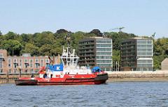 Roter Hafenschlepper vor dem Elbufer  von Hamburg Altona Altstadt.