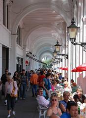 Strassengastronomie in den Hamburger Alsterarkaden - Hamburg Touristen flannieren durch den Bogengang, andere sitzen an Tischen an der Kleinen Alster.