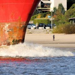 Schiffsbug in Fahrt - Gischt; Spaziergänger am Sandstrand in Hamburg Blankenese.