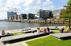 Sommersonne in der Hamburger Hafencity - Hamburg Touristen und Besucher der Hafencity sitzen am Marco Polo Platz - im Hintergrund die Baustelle der Elbphilharmonie und die modernen Wohngebäude am Dalmannkai.
