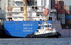 Der Containerfeeder HOOGE mit Heimathafen Gibraltar legt mit Hilfe eines Schleppers CONSTANT vom Hafenkai im Hamburger Hafen ab.