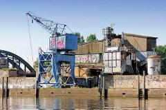 Baustoffhandlung am Billehafen in Hamburg Rothenburgsort; Kran am Kai - Grafitti, im Hintergrund die Billhorner Brückenstrasse über den Oberhafenkanal.