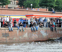 Kaimauer am Altonaer Fischmarkt - Besucher sitzen in der Sonne am Wasser des Altonaer Hafens.