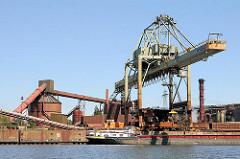 Ein Binnenschiff liegt mit einer Ladung Schrott im Hamburger Dradenauhafen - mit dem Kran und einem Schrottmagneten wird der Rohstoff an Land gebracht.