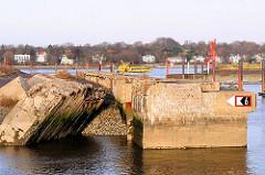 Mauerreste des ehem. U-Bootbunkers Fink II im Rüschkanal von Hamburg Finkenwerder - im Hintergrund eine Fähre mit Fahrt Richtung Anleger Finkenwerder.