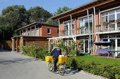 Neubausiedlung / Passivhäuser im Zassenhausweg - ein Briefträger fährt mit seinem Postfahrrad  seine Zustelltour.