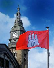 Hamburg Flagge im Wind vor dem Uhrenturm des Hamburger Hauptbahnhofs.