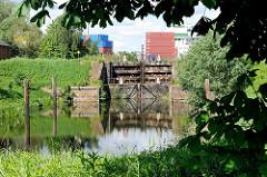Historische Schleuse des Schmidtkanals in Hamburg Wilhelmsburg - Containerlager im Hintergrund.