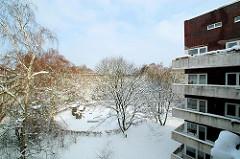 Blick im Winter auf einen der Spielplätze im Hölderlinspark in der Jarrestadt von Hamburg Winterhude. Rechts ein Ausschnitt vom Schneiderblock mit Balkons an der Stammannstrasse.