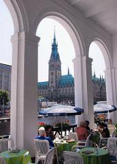 Blick durch die Arkadenbögen über die Kleine Alster auf das Hamburger Rathaus.