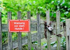 """Schild """"Warnung vor dem Hunde"""" - Staketenzaun / Stakententor mit Kette und Schloss gesichert - Stadtteilfotos aus Hamburg Gut Moor."""