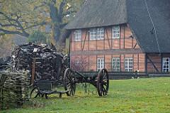 Feuerholzstapel und Karren auf einer Wiese hinter dem Volksdorfer Museumsdorf.