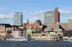 St. Pauli Landungsbrücken - Schiffe der Hafenrundfahrt am Anleger - neue und historische Architektur am Elbufer in Hamburg St. Pauli.
