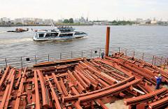Eisenträger liegen auf einem Ponton am Kai der Baustelle der Elbphilharmonie - Fahrgastschiff der Hafenrundfahrt Hamburg.