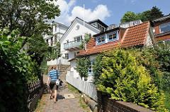 Fussweg mit Kopfsteinpflaster im Treppenviertel von Hamburg Blankenese - Grünpflanzen in den Vorgärten der Häuser.