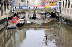 Blick vom Bleichenstieg zur Bleichenbrücke - das Wasser des Fleets ist abgelassen; Arbeitsboote liegen im Schlamm - ein Mitarbeiter geht durch das Schlick zu den Booten.
