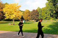 Herbst im Eppendorfer Park - Bäume mit strahlend gelben Herbstblättern in der Herbstsonne - Jogger laufen auf einem der Wege in der Grünanlage in Hamburg Eppendorf.