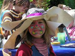 Sommerfest in der Jarrestadt - Kinderschminken in der Sonne auf dem Schulplatz. Ein bunt geschminktes Mädchen lacht.