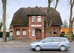 Kneipe Zum Dorfkrug - Backsteingebäude in der Neuwiedenthaler Strasse in Hamburg Hausbruch; fahrendes Auto.