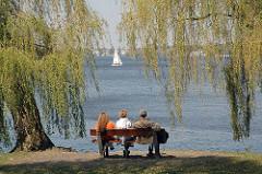 Parkbank an der Alster - Entspannung am Alsterufer - Frühlingssonne und zartes Grün der jungen Weidenblätter.
