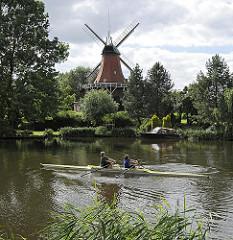 Wahrzeichen von Hamburg Reitbrook - Windmühle an der Dove Elbe - Ruderboot bei Trainingsfahrt.