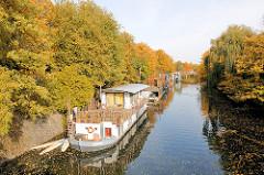 Neues Wohnen in Hamburg - Wohnen auf dem Wasser - moderne Hausboote auf dem Eilbekkanal; herbstlich gefärbte Bäume am Ufer des Kanals.