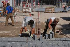 Bauarbeiten an dem entstehenden Beatles Platz Hamburg St. Pauli - Bauarbeiter verlegen Pflastersteine.
