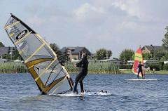 Windsurfen in Hamburg  - Wassersport auf dem Oortkatener See - Windsurfer mit Surfbrett und Windsurfsegel auf dem Wasser.