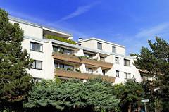 Balkons eines Neubaugebäudes zwischen Bäumen und Sträuchern.