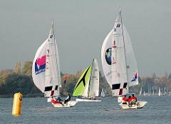Segelboote mit Spinnaker - Segelregatta auf der Aussenalster - vorm Alsterufer von Hamburg Harvestehude.