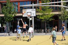 Jugendliche spielen Basketball in der Hafencity - ein Schild am Korb weist auf die Spielzeiten hin.