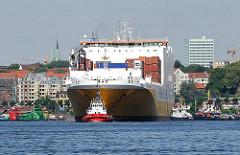 Ein RoRo Frachtschiff wird in den Hamburger Hafen eingeschleppt - im Hintergrund Gebäude an der Strasse St. Pauli Fischmarkt.
