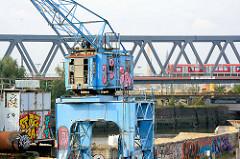 Hafenkran am Kai des Billehafens in Hamburg Rothenburgsort; S-Bahnzug auf der Brücke.
