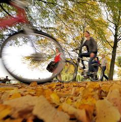 Herbstlaub an der Alster - Spaziergänger und Fahrradfahrer in Hamburg St. Georg.