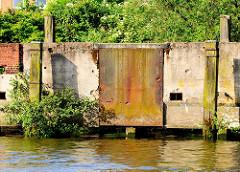 Verrostete Eisenplatte an einer Betonkaimauer - Holzdalben mit jungen Bäumen bewachsen -  Relikte / Überbleibsel vom alten Hamburger Hafen.