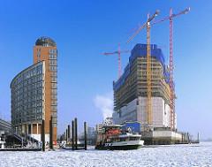 Baustelle der Elbphilharmonie im Winter - Entstehung der Hafencity - Bausstelle im Hamburger Hafen. Baukräne am Kaispeicher.