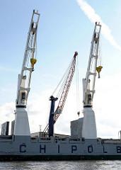 Frachtschiff mit bordeigener Kränen und Kaikran im Hamburger Hafen - Oderhafen am Oderhöft im Stadtteil Steinwerder.