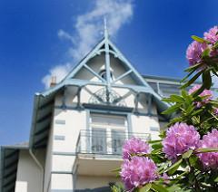 Blühender Rhododendron - Hausgiebel mit Schnitzereien.