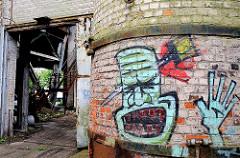 Industrieruine in Hamburger Stadtteil Wilhelmsburg - eine Ziegelmauer ist mit Grafitti besprüht.
