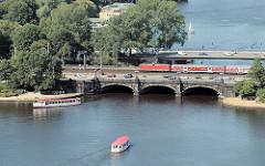 Luftaufnahme Lombardsbrücke - Alsterschiffe fahren auf der Binnenalster - ein Vorortszug überquert die historische Hamburger Brücke, die die Grenze zwischen den Stadtteilen Neustadt und Altstadt darstellt.
