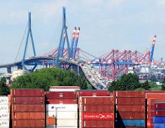 Blick über ein Containerlager in Hamburg Wilhelmsburg zu der Köhlbrandbrücke und den Containerbrücken des Terminals Burchardkai.