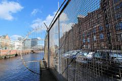 Zollzaun mit Maschendraht am Zollkanal des Hamburger Freihafens - hinter dem Zaun Gebäude der Speicherstadt und der Schriftzug der Hamburg Port Authority / HPA