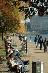 Sonntagnachmittag im Herbst in Hamburg - die Hamburger und Hamburgerinnen gehen an der Alster spazieren oder setzen sich auf die Parkbänke um die Herbstsonne zu geniessen,