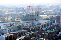 Blick über die Kupferdächer der Speicherstadt und den modernen Wohnhäusern am Sandtorkai zur entstehenden Elbphilharmonie - Fotos aus der Hamburger Hafencity.