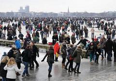 Hamburger Eisvergnügen auf der Aussenalster am Alsterufer - Menschenmassen bevölkern das dicke Eis der Hamburger Aussenalster.