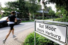 Stadtteilschild GUT MOOR - Bezirk Harburg; ein Jogger läuft entlang der Strasse - Fotos aus den Hamburger Stadtteilen.