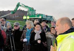 Rede Hamburger Bürgermeister Olaf Scholz anlässlich des Abbaus des Zollzauns bei der Harburger Chaussee / Spreehafen  - im Hintergrund steht ein Bagger auf dem Deich.